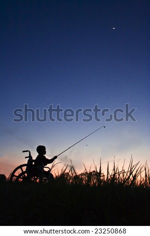 Silhouette of boy in wheel chair fishing at sunset