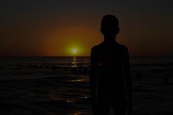 Silhouette of boy on sea sunset