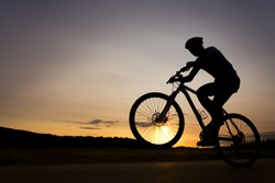 Silhouette of boy on the bike. Young cyclist is jumping on his bike during sunset. Fore wheel is over the horizon.