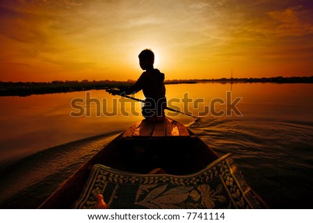 Silhouette of boy paddling boat at sunset