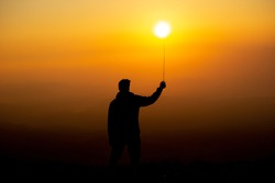 silhouette of boy playing with sun in the golden orange background. Dawn in mountain area. Boy holding sun as a Balloon with stick or as a fireball in hand