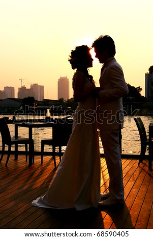 Silhouette of Bride and Groom kissing on the romantic wedding along Chaophraya River , bangkok Thailand