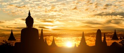Silhouette of Buddha on golden temple sunset background. Travel attraction in Thailand.