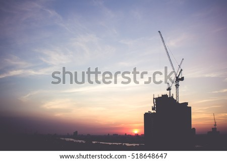 silhouette of building under construction with crane during sunset, vintage filter