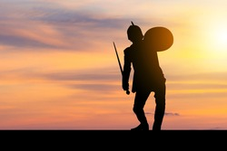 Silhouette of Business man in Knight Sword and Shield costume with clipping path sunset background, Fighting Business Warrior Concept.