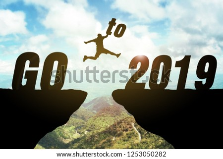 Silhouette of business man jump between cliff. keep go on to success concept at 2019 is coming over a beautiful high view mountain background. ready in 2019 years. GO TO 2019 YEAR CONCEPT #1253050282