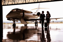 Silhouette of Businessman and Businesswoman walking away from the private jet in hangar