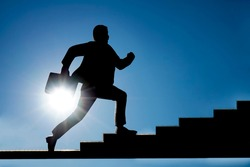 silhouette of Businessman figure with case running up steep stairs. sunny heaven background. Concept of career growth. sunlight and blue sky background.