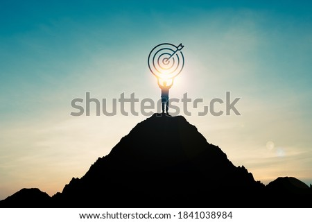 Silhouette of businessman holding target board on the top of mountain with over blue sky and sunlight. It is symbol of leadership successful achievement with goal and objective target.