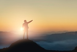 Silhouette of businessman on mountain with sunset sky background. Business success and leadership concept.