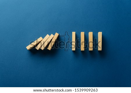 Silhouette of businessman on navy blue background stopping falling dominos in a conceptual image. With copy space.