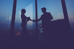Silhouette of businessman shaking hands in honor of the transaction with his new woman partner, male and female entrepreneurs congratulate each other with their successful work