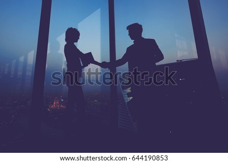 Silhouette of businessman shaking hands in honor of the transaction with his new woman partner, male and female entrepreneurs congratulate each other with their successful work Photo stock ©