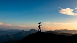 silhouette of businessman with flag on mountain top over sunset sky background, business, success, leadership and achievement concept