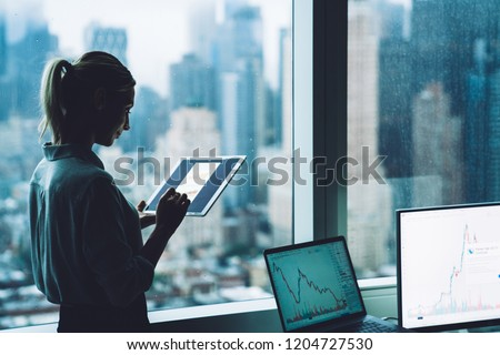 Silhouette of businesswoman standing in office interior near skyscraper window with touch pad in hands. Woman economist checking stock exchange currency via online financial resources on modern tablet
