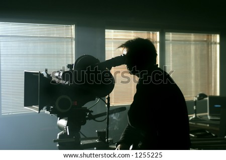 Silhouette of cameraman with the camera in the darkness