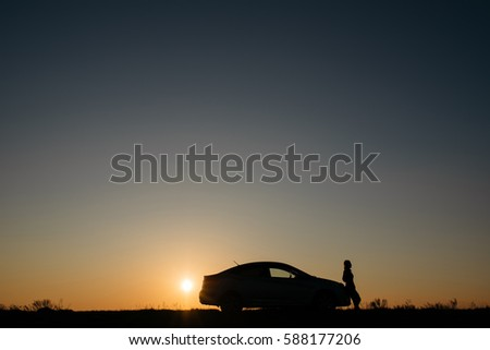 silhouette of car and girl at sunset