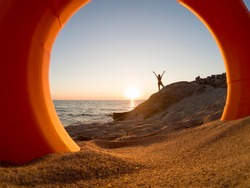 Silhouette of cheerful woman standing on rock with her arms spread open by the seaside in sunset or sunrise. Photo trough rescue buoy.