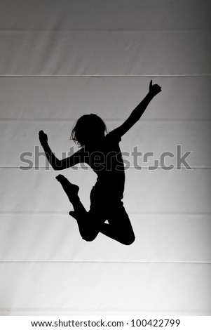 silhouette of child jumping on trampoline