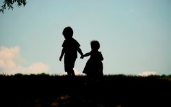 Silhouette of children holding hands