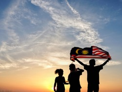 Silhouette of children waving the national flag in conjunction with Malaysia Independence Day. Selective focus.