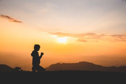 Silhouette of Christian woman praying worship at sunset. Christian Religion concept background. Hands  in prayer. worship god with religion concept.