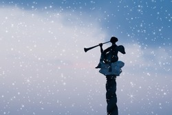 Silhouette of christmas angel on dark blue evening sky. Defocused photo as background for your design