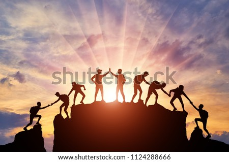 Silhouette of climbers who climbed to the top of the mountain thanks to mutual assistance and teamwork. Conceptual scene of a team of alpinists