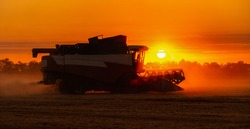 Silhouette of combine harvester on the field at sunset.