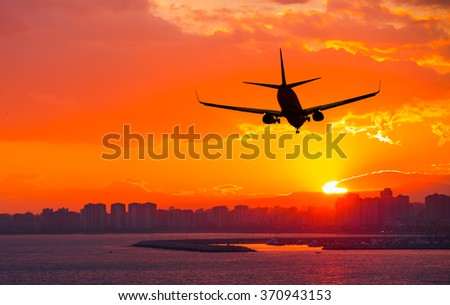 silhouette of commercial plane flying over a city during sunrise - Shutterstock ID 370943153