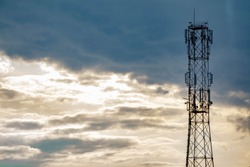Silhouette of communication tower with cloudy sky with space for text. Mobile phone 5G tower in windy sky background. Isolated signal transmitter broadcasting. Tower antenna construction for signal.