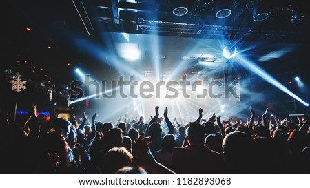 silhouette of concert crowd in front of bright stage lights. Dark background, smoke, concert  spotlights, disco ball