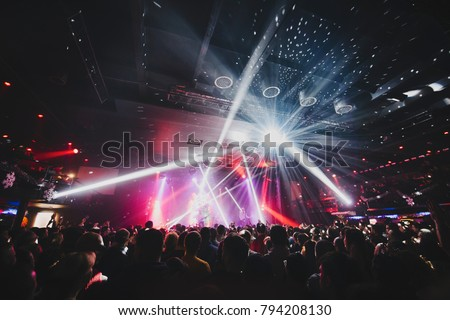 silhouette of concert crowd in front of bright stage lights. Dark background, smoke, concert  spotlights, disco ball #794208130