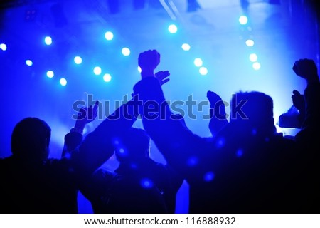 Silhouette of concert crowd in front of stage lights