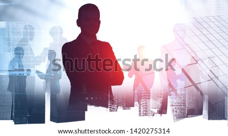 Silhouette of confident business leader with his colleagues over abstract city background. Concept of leadership. Toned image double exposure