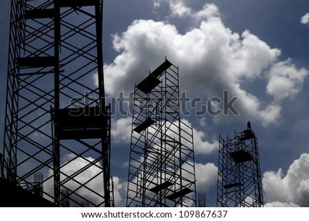 Silhouette of construction scaffolding against a blue cloudy sky.