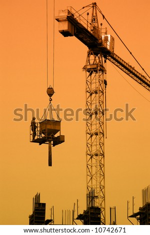 Silhouette of construction worker being transported by jib crane with concrete mix charging hopper against sunset sky