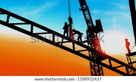 silhouette of construction worker working on hoist crane
