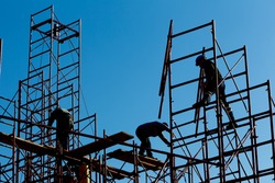 silhouette of construction workers against sky on scaffolding with ladder on building site