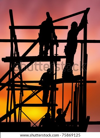 Silhouette of construction workers on scaffold working against a vivid and colorful sunset