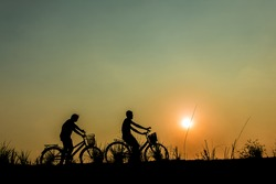 silhouette of couple driving bike happy time sunset