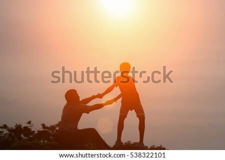silhouette of couple help each...