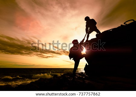 silhouette of couple helping...