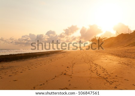 Silhouette of couple taking a walk on beach in sunset