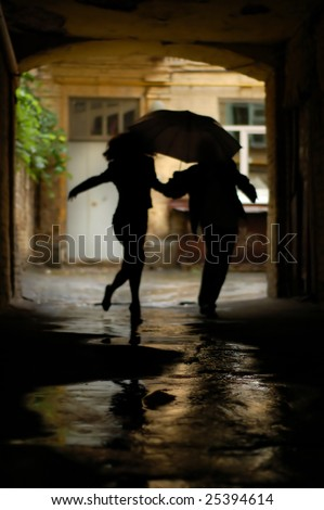 silhouette of couple with umbrella running from rain