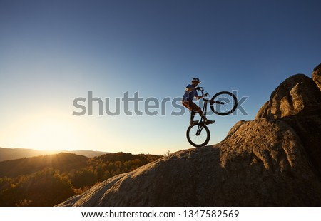 Silhouette of courageous cyclist balancing on back wheel on trial bicycle. Professional sportsman biker making acrobatic stunt on the top of mountain at sunset. Concept of extreme sport. Copy space #1347582569