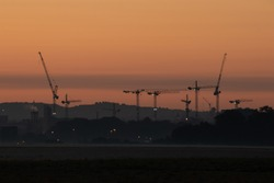 Silhouette of crane tower on the construction site with city building background in sunset sky. Phoenix Park Dublin, Ireland Europe
