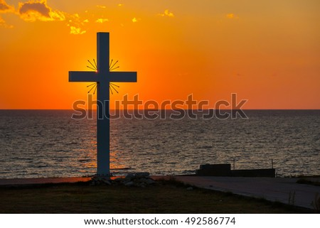 Silhouette of cross at sunrise or sunset with light rays and sea panorama, Greece #492586774