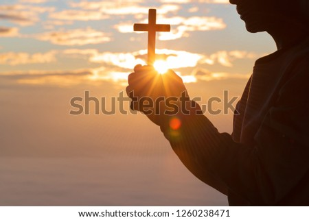 Silhouette of cross in human hand, the background is the sunrise., Concept for Christian, Christianity, Catholic religion, divine, heavenly, celestial or god.