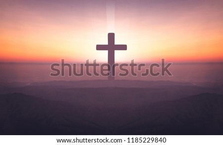 Silhouette of crucifix cross on mountain at sunset time with holy and light background.